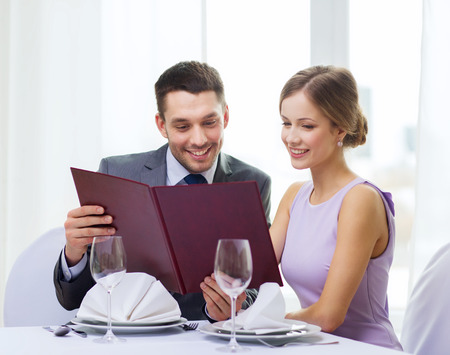 couple dining: restaurant, couple and holiday concept - smiling couple with menu at restaurant Stock Photo