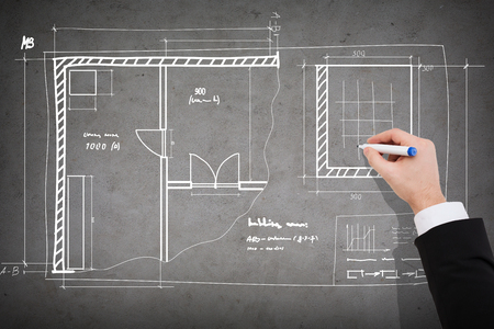 business and architecture concept - close up of businessman drawing blueprint on concrete wall photo