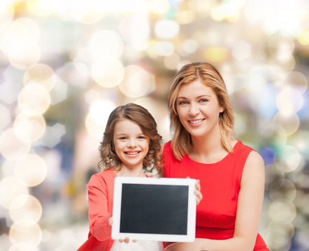 family, child and technology concept - smiling mother and daughter with tablet pc computers blank black screen photo
