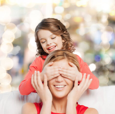 family, child and happiness concept - smiling mother and daughter making a joke photo
