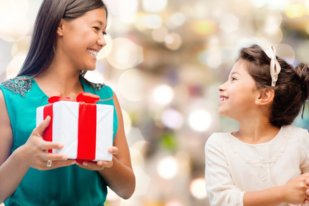 holidays, presents, christmas, family, child and x-mas concept - happy mother and child girl with gift box photo