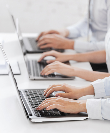 computer center: business, school and education concept - group of people working with laptops in office