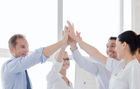幸せなビジネスのオフィスに与える高 5 をチーム成功と勝利の概念-