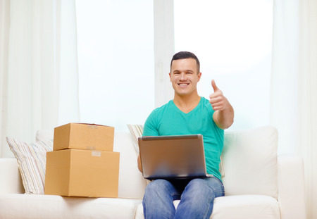 technology, home and lifestyle concept - smiling man with laptop and cardboard boxes at home showing thumbs up photo