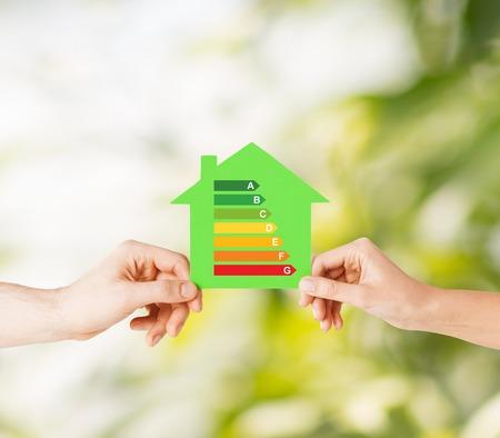 energy saving: ahorro de energía, los bienes raíces y el concepto de hogar - primer plano de las manos de pareja que sostienen la casa de papel verde con clasificación de eficiencia energética Foto de archivo