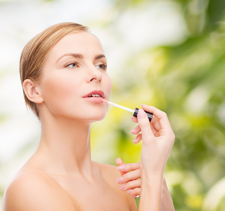 eco sensitive: cosmetics, health and beauty concept - beautiful woman with pink lipgloss