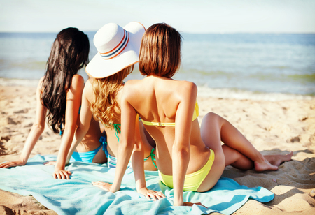 summer holidays and vacation - girls sunbathing on the beach photo