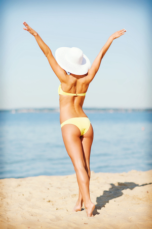 summer holidays, vacation and beach concept - girl in bikini posing on the beach photo