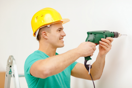 repair, building and home concept - smiling man in yellow protective helmet with electric drill making hole in wall photo