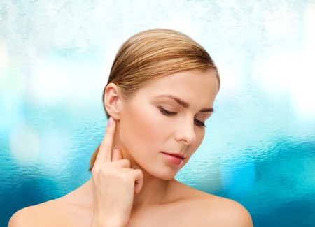 health and beauty concept - face of beautiful woman touching her ear photo
