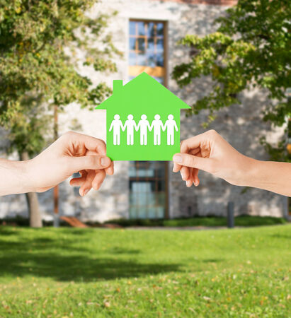 real estate and family home concept - isolated closeup picture of male and female hands holding green paper house photo