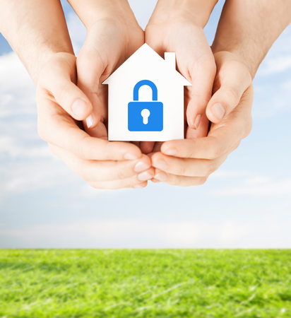 safe house: real estate and family home security concept - closeup picture of male and female hands holding white paper house with blue lock