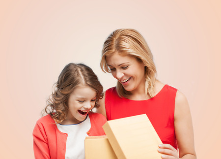 family, child, holiday and party concept - smiling mother and daughter with opening gisft box photo