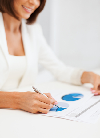 business, education, school, documents, people concept - businesswoman or student working with graphs in office photo