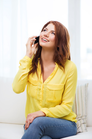 home, technology and communication concept - smiling woman with smartphone sitting on couch at home photo