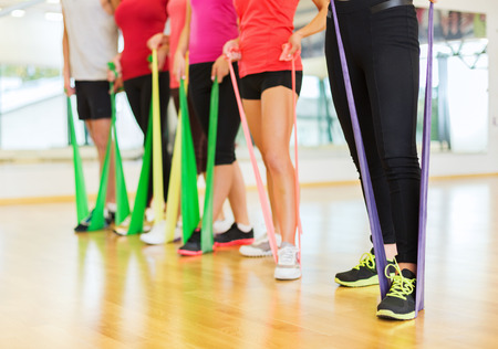 resistance: fitness, sport, training, gym and lifestyle concept - group of people with working out with rubber bands in the gym