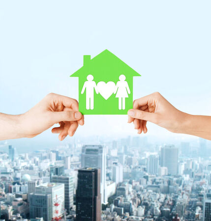 real estate and family home concept - isolated picture of male and female hands holding green paper house with family photo