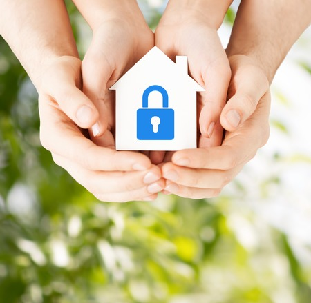 Bienes raíces y el concepto de familia de la seguridad casera - de cerca la imagen de las manos masculinas y femeninas que sostiene la casa de papel blanco con bloqueo de color azul Foto de archivo - 27759530