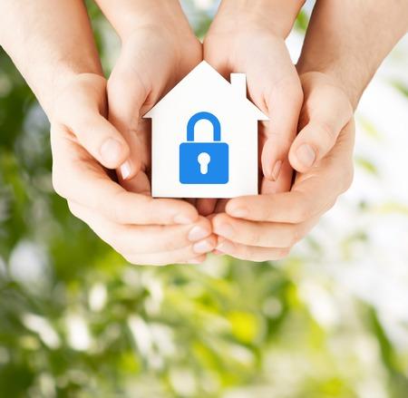 vastgoed en familie binnenlandse veiligheids concept - close-up beeld van mannelijke en vrouwelijke handen die witte papier huis met blauwe slot Stockfoto
