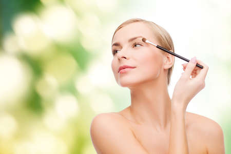 cosmetics, health and beauty concept - beautiful woman with makeup brush Stock Photo