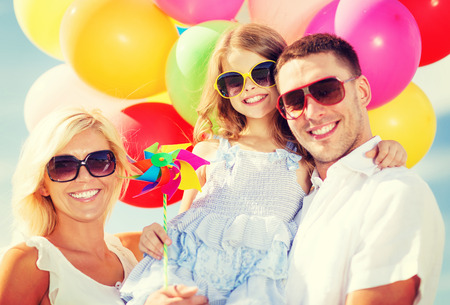 summer fun: summer holidays, celebration, children and people concept - family with colorful balloons