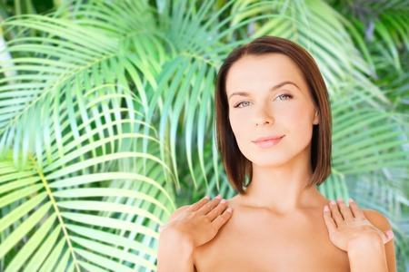 beauty, spa, health and people concept - beautiful woman touching her shoulders Stock Photo