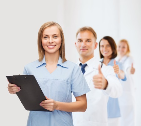 nurse clipboard: healthcare and medicine concept - smiling female doctor or nurse with clipboard Stock Photo