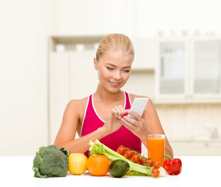 dieting, food, healthcare and technology concept - smiling sporty woman with fruits and vegetables counting calories in smartphone photo
