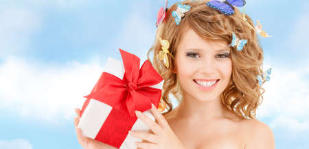 health, holidays and beauty concept - happy teenage girl with butterflies in hair showing gift box photo