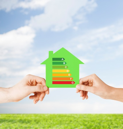 alternative energy source: energy saving, real estate and family home concept - closeup of couple hands holding green paper house with energy efficiency rating
