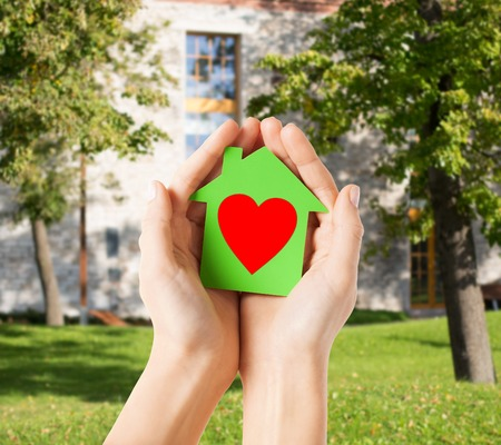 charity, real estate and family home concept - closeup picture of female hands holding green paper house with red heart Stock Photo