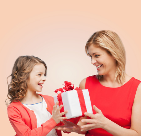 nice day: family, child, holiday and party concept - smiling mother and daughter with gift box