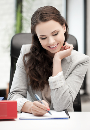 happy woman with documents writing something down photo