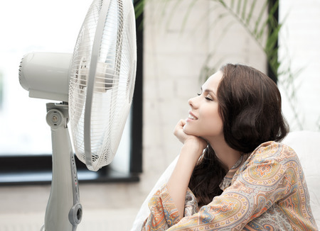 home technology concept - happy and smiling woman sitting near ventilator photo