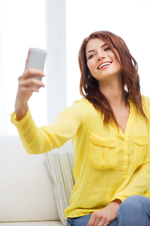 home, technology and internet concept - smiling woman with smartphone sitting on couch at home photo