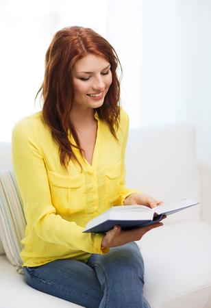 leasure: leasure e concetto di casa - sorridente ragazza adolescente leggendo il libro e seduto sul divano a casa Archivio Fotografico