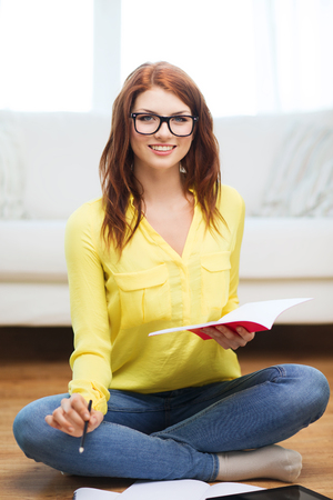 business, education and technology concept - smiling female student in eyeglasses with notebooks and tablet pc computer at home photo