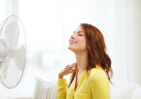 estado del tiempo: verano, tiempo y concepto equipemt - sonriente adolescente pelirroja con ventilador grande en casa