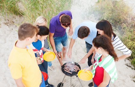 summer, holidays, vacation, happy people concept - group of friends having picnic and making barbecue on the beach photo