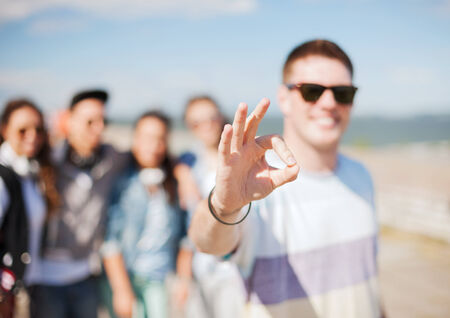 ok sign: summer holidays and teenage concept - close up of male hand showing ok sing with fingers Stock Photo