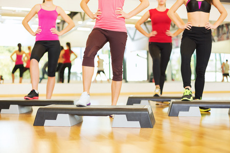 step fitness: fitness, sport, training, gym and lifestyle concept - close up of women legs steping on step platform in gym