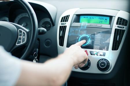electronics: transportation and vehicle concept - man using car control panel Stock Photo