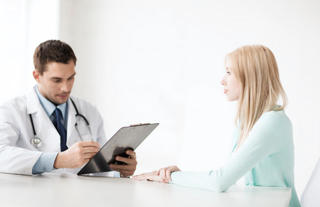serious doctor: healthcare and medical concept - male doctor with patient in hospital