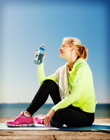 girl sit: sport and lifestyle concept - woman drinking water after doing sports outdoors