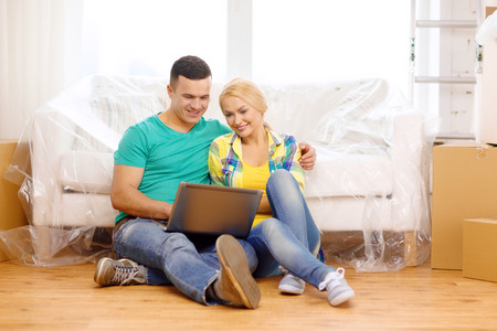 moving, home, technology and couple concept - smiling couple with laptop sitting on floor in new house photo