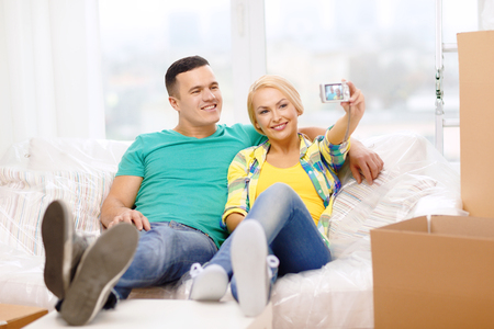 moving, home and couple concept - smiling couple relaxing on sofa taking picture with digital camera in new home photo