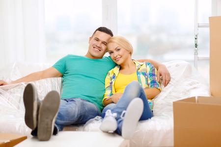 moving, home and couple concept - smiling couple relaxing on sofa in new home Stock Photo