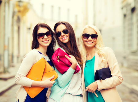 clutches: holidays and lifestyle concept - beautiful girls with bags in the ctiy