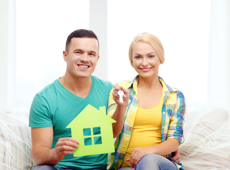 moving, home and couple concept - smiling couple with green house and keys in new home photo