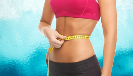 six girls: fitness, diet and body parts concept - close up of trained belly with measuring tape